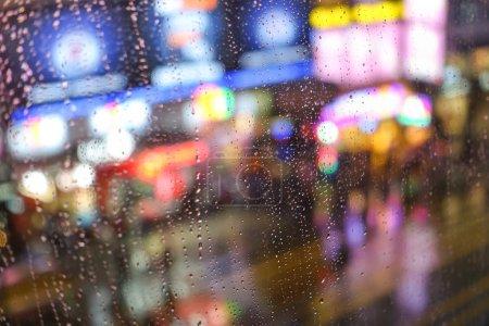 Photo pour Fond abstrait émotionnel avec des lumières défocalisées bokeh à NathanRoad à Hong Kong derrière les gouttes de pluie dans le verre de fenêtre - Focus sur quelques gouttes en raison de la faible profondeur de champ - image libre de droit