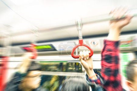 Concept of metropolitan transportation during rush hour - Hong Kong underground with radial zoom defocusing and vintage filtered look - Focus on the hand holding train handle during subway trip