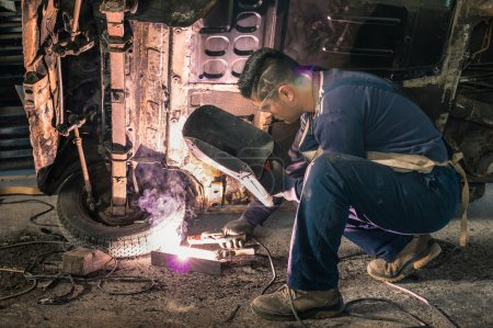 Young man mechanic worker repairing old vintage car body in messy garage - Safety at work and protection wear - Guy with cool hair cut at vehicle renovation - Soft focus with natural light lens flare