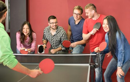 Group of happy young friends playing ping pong table tennis - Fun moment in game room of traveler youth hostel - Concept of vintage sport and genuine emotions - Main focus on two guys with eye glasses