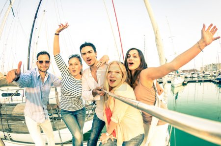 Best friends using selfie stick taking pic on exclusive luxury sailing boat - Concept of friendship and travel with young people and new technology  trends - Bright nostalgic desaturated color tones