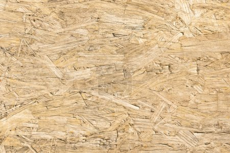 Chipboard wood background and alternative construction material - Texture on wooden panel in construction yard - Retro seamless backdrop pattern - Pressed particleboard for house isolation coating