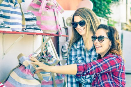 Young beautiful women girlfriends at flea market looking for bags - Best friends sharing free time having fun and shopping during travel - Soft vintage marsala filtered look - Focus on smallest girl