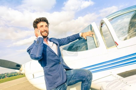 Young handsome man talking with mobile smart phone at private airplane - Modern business concept with confident guy using smartphone at airport - Modified paintings on air plane and tilted horizon