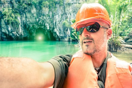 """Handsome man taking selfie at """" Puerto Princesa """" underground river caves - Travel concept in Palawan Philippines - Warm greenish tones with focus on face of the guy and soft defocused background"""