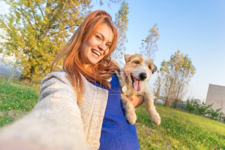 Young redhead woman taking selfie outdoors with cute dog - Concept of friendship and love with people and animals together - Sunny winter afternoon with warm color tones - Tilted horizon composition