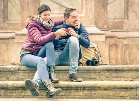Happy young couple having fun with smartphone outdoors - Dating and flirting concept with hipster best friends interacting with new technology - Beginning of a love story on warm vintage filtered look