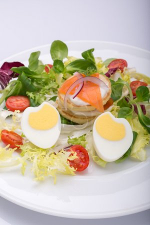 green salad with eggs in the shape of a heart, salmon, cherry tomatoes