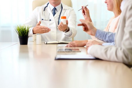 hospital, medical education, health care, people and medicine concept - doctor showing meds to the  group of happy doctors at medical office
