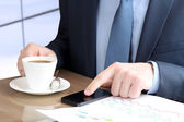 Young businessman working with mobile phone.Graphs  and coffee b