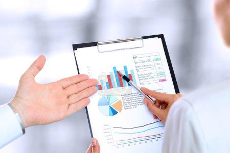 Foto de Los colegas de trabajo y análisis de cifras financieras - Imagen libre de derechos