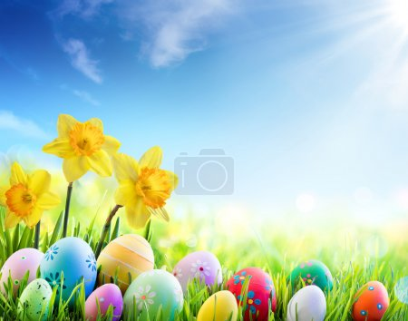 Daffodils And Colorful Decorated Eggs On The Sunny Meadow - Easter Holiday Background