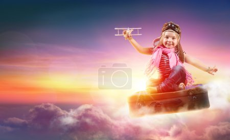 Photo for Child Flying With Fantasy On Suitcase In The Sky - Royalty Free Image
