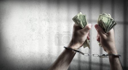 arrest for corruption - man handcuffed holding dollars