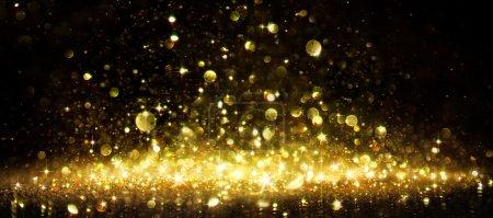 Photo pour Miroitement de paillettes d'or sur fond noir - image libre de droit