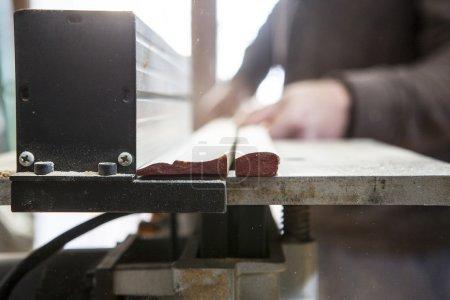 Photo pour Menuisier travaillant avec jambages à l'aide de la table de la scie circulaire électrique. Particules de sciure de bois sont visibles sur l'air - image libre de droit