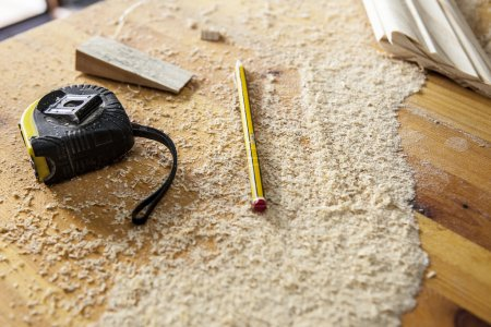 Photo pour Outils de charpentier. Ruban à mesurer, crayon de marquage et une cale sur la sciure de bois - image libre de droit