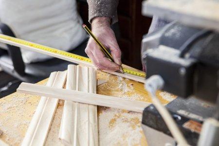Photo pour Menuisier travaillant avec des jambages. Il est mesure de bois et marquer avec un crayon - image libre de droit
