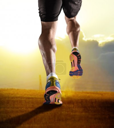 close up feet with running shoes and strong athletic legs of sport man jogging in fitness training sunset workout