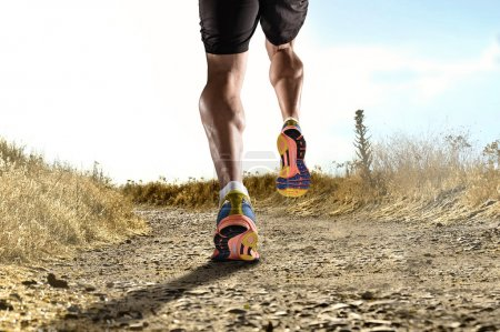 close up feet with running shoes and strong athletic legs of sport man jogging in fitness training workout
