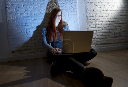 scared female teenager with computer laptop suffering cyberbullying and harassment being online abused