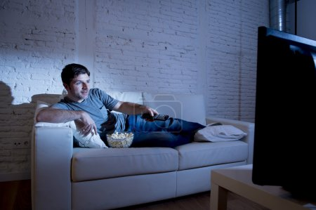 young attractive man at home lying on couch at living room watching tv holding remote control