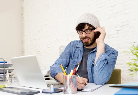 hispanic attractive hipster businessman working at home office talking on mobile phone