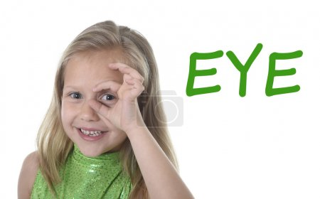 cute little girl circling eye in body parts learning English words at school