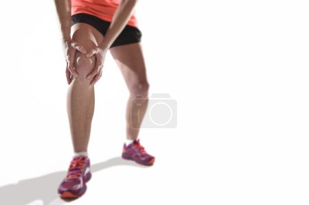 young sport woman with strong athletic legs holding knee with hands in pain suffering ligament injury