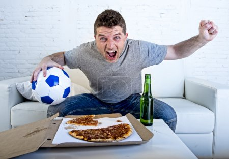 young man holding ball watching football game on tv at home couch with pizza and beer celebrating crazy goal or victory