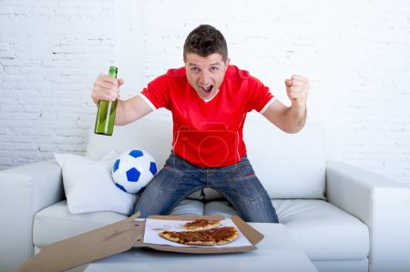 man watching football game on tv in team jersey celebrating goal crazy happy jumping on sofa