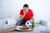 man alone holding ball with beer and pizza in stress wearing team jersey watching football game on tv