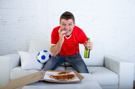 young man alone holding beer bottle eating pizza in stress wearing team jersey watching football tv