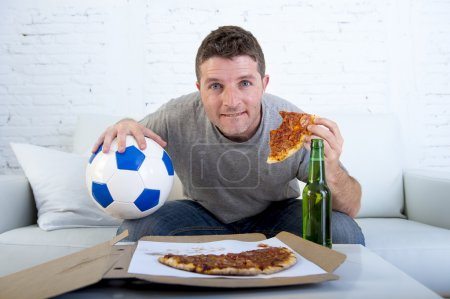 man in stress watching football game on television eating pizza drinking beer looking excited and anxious