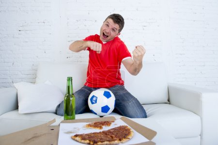 young football fan man watching game on tv in team jersey celebrating goal crazy happy on couch