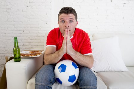 Young man watching football game on tv nervous and excited suffering stress praying god for goal
