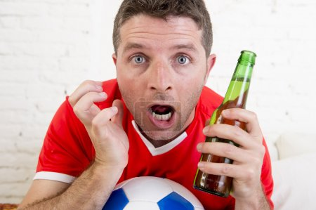 close up face fan man watching football on tv in team jersey suffering nervous