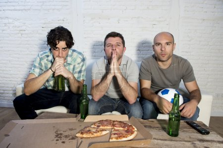 friends fanatic football fans watching tv match with beer bottles and pizza suffering stress