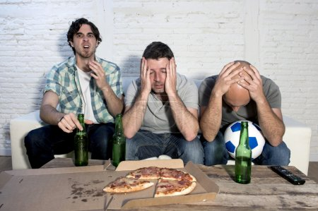sad frustrated friends fanatic football fans watching tv match with beer dejected