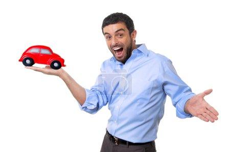 Photo pour Jeune homme séduisant heureux pointant voiture gros jouet rouge dans sa main isolé sur fond blanc en assurance automobile, nouvelle automobile achat et la location de concept - image libre de droit