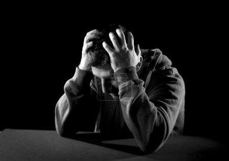 Photo for Young desperate man suffering with hands on head in deep depression, pain , emotional disorder, grief and desperation concept isolated on black background with grunge studio lighting in black and white - Royalty Free Image