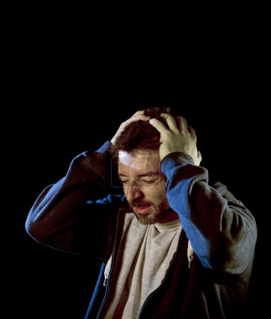 Photo for Young desperate man suffering with hands on head in deep depression, pain , emotional disorder, grief and desperation concept isolated on black background with grunge studio lighting - Royalty Free Image