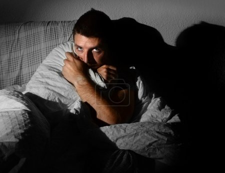 Photo for Young sick looking man sitting on couch at home in scary and desperate looking suffering insomnia, depression, nightmares, emotional crisis or mental disorder with a dim light and deep dark shadow on the wall - Royalty Free Image