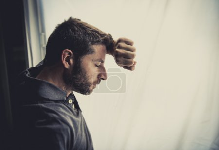 Young attractive man leaning desperate on window g...