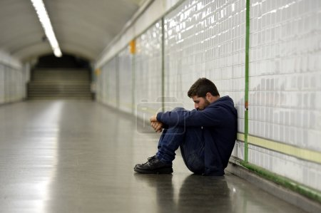 Photo for Young man abandoned lost in depression sitting on ground street subway tunnel suffering emotional pain, sadness and looking destroyed and desperate leaning on wall alone - Royalty Free Image