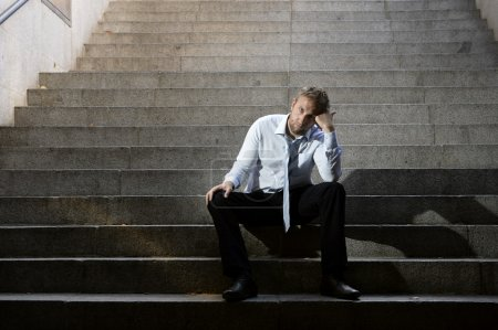 Businessman crying lost in depression sitting on street concrete stairs