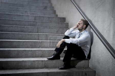 Photo for Young business man crying abandoned lost in depression sitting on ground street concrete stairs suffering emotional pain, sadness, looking sick in grunge lighting - Royalty Free Image