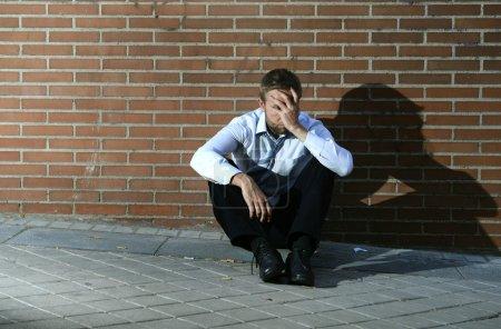 Photo pour Les homme d'affaires jeune qui a perdu emploi abandonné perdu dans la dépression, assis sur le coin de la rue au sol contre le mur de briques, souffrant de douleur émotionnelle, penser et de pleurer seul - image libre de droit