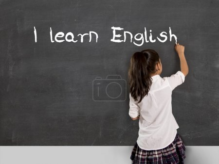 schoolgirl writing I learn English with chalk on blackboard school