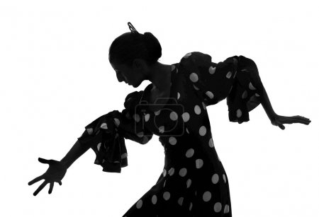 Photo for Silhouette of Spanish woman Flamenco dancer dancing Sevillanas in gypsy dots dress and comb in traditional Dance of Spain concept performing show isolated on white background - Royalty Free Image